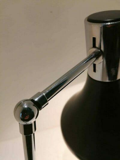 Gros plan de la rotule chromée de la lampe vintage au design scandinave des années 50/60 par ARNE JACOBSEN. Acier laqué noir et chrome. Orientable dans différentes positions par ses deux rotules.